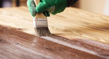 Ein Holzzaun, welcher gerade mit einem Pinsel neu lackiert wird.