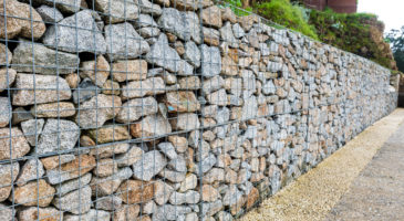Ein Zaun aus Steinen an einer Straße zum Lärmschutz